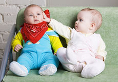 Two babies sitting on a sofa together Royalty Free Stock Image
