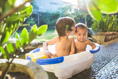 Two babies taking a bath together. Two happy babies taking a bath playing together. Little child in a bathtub stock photography