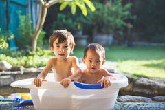 Two babies taking a bath together. Two happy babies taking a bath playing together. Little child in a bathtub royalty free stock photography