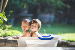 Two babies taking a bath together. Two happy babies taking a bath playing together. Little child in a bathtub stock images