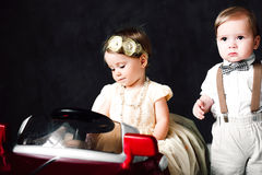 Two babies wedding - boy and girl dressed as bride and groom playing with toy car Royalty Free Stock Photography