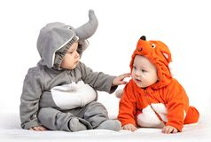 Two baby boys dressed in animal costumes playing. Over white background Royalty Free Stock Photography