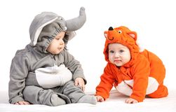Two baby boys dressed in animal costumes on white. Two baby boys dressed in animal costumes over white background Stock Photos