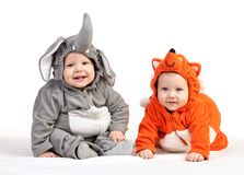 Two baby boys dressed in animal costumes on white. Two baby boys dressed in animal costumes over white royalty free stock image