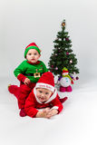 Two baby boys dressed as Santa Claus and Santas He. Lper lying next to Christmas tree. White background Stock Photography
