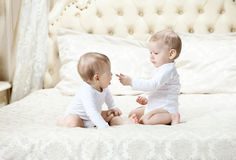 Two baby boys playing on bed Stock Photography