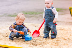 Two baby boys playing with sand in a sandbox Stock Image