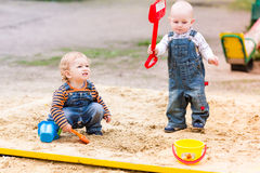 Two baby boys playing with sand. In a sandbox Royalty Free Stock Photography