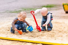 Two baby boys playing with sand. In a sandbox Stock Photo