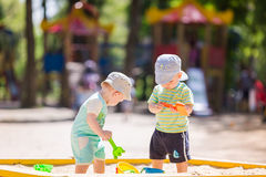 Two baby boys playing with sand Stock Images
