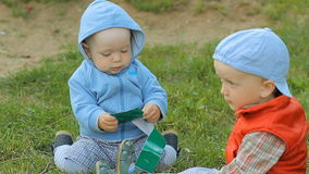 Two baby boys playing together on the lawn in the park stock footage