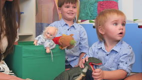 Two baby boys playing with toys in their nursery room stock footage