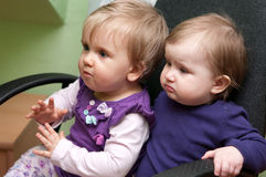 Two baby girls in chair. Portrait of two baby girls sitting together in a chair Royalty Free Stock Images