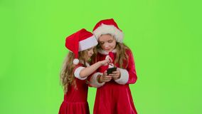 Two baby girls look at the pictures on the phone and laugh. Green screen. Two baby girls in New Year costumes and red caps look at the pictures on the phone and stock video footage