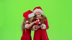 Two baby girls look at the pictures on the phone and laugh. Green screen. Slow motion. Two baby girls in New Year costumes and red caps look at the pictures on stock footage