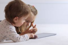 Two baby girls lying on bed with a tablet, close-up view royalty free stock photo