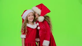 Two baby girls in New Year costumes tell each other secrets. Green screen. Slow motion. Two baby girls in New Year costumes and red hats tell each other secrets stock video