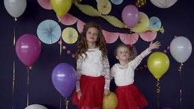 Two baby girls sisters waving and celebrating on birthday party stock video