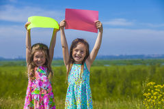 Two baby girls in summer dresses on the nature of holding the co Royalty Free Stock Photography