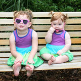 Two baby girls in sunglasses and sun dresses Royalty Free Stock Photo