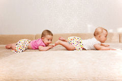 Two baby twins crawling one after another. On the sofa stock photos