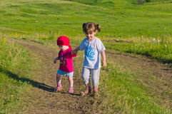 Two baby walking in a field Royalty Free Stock Photos