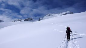 Two backcountry skiers on a tour in the Austrian Alps and putting in new tracks on their way to the summit Stock Image
