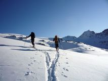 Two backcountry skiers on a tour in the Austrian Alps and putting in new tracks on their way to the summit. A view of two backcountry skiers on a tour in the Stock Photo