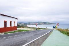 Two backpacker travelers walk on road in city on seaside Stock Image