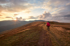 Two backpackers fall on the trail in the mountains. Two hikers with backpack walking along the trail on the mountain top at sunset time. Travel lifestyle concept Stock Photo