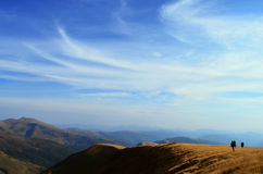 Two backpackers hiking in mountains royalty free stock photography