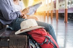 Two backpackers look at a map. At train station stock images