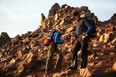 Two backpackers in morning mountains Royalty Free Stock Photo
