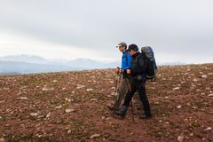 Two backpackers in mountains Stock Image