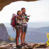 Two backpackers in mountains. Young couple examining the surroundings. The guy holding the camera, she shows off into the distance. Photos of the cave Royalty Free Stock Photos