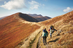 Two backpackers on the trail in the mountains. Rear view of two young people walking down the trail path on mountain. Two girls hiking with backpacks. Ukraine Stock Images