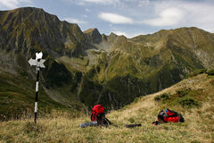 Two backpacks loaded next to a pole with arrows. In a wild mountain scenery Stock Photo