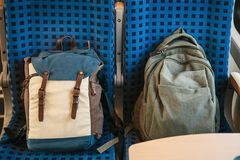 Two backpacks on the seats in the train royalty free stock images
