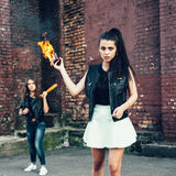 Two Bad fan girls with Molotov cocktail bomb in the street Royalty Free Stock Images