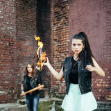 Two Bad girls hooligans with Molotov cocktail bomb in the street Royalty Free Stock Image
