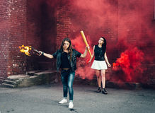Two Bad girls with Molotov cocktail and red smoke bomb Stock Image