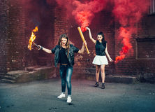 Two Bad girls with Molotov cocktail and red smoke bomb Stock Images