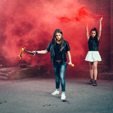 Two Bad girls with Molotov cocktail and red smoke bomb Royalty Free Stock Image