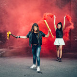 Two Bad girls with Molotov cocktail and red smoke bomb Royalty Free Stock Photography