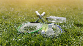Two badminton rackets and a bottle of water. Shot at sunset Royalty Free Stock Photos