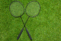 Two badminton rackets lying crossed on the grass Royalty Free Stock Images