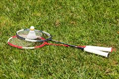 Two badminton rackets and shuttlecock on the grass Stock Photo