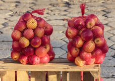 Two bags full of delicious red apples standing on a wooden chest Royalty Free Stock Images