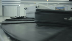 Two bags move along the luggage conveyor. Close-up. The camera focuses on the luggage belt of the baggage claim desk at the airport. The luggage conveyor moves stock footage