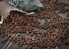 Two bags of roasted arabica coffee beans. On a dark wooden background Royalty Free Stock Photo